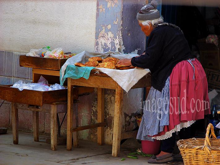 Vieille femme tenant un tout petit commerce sur le pas de sa porte