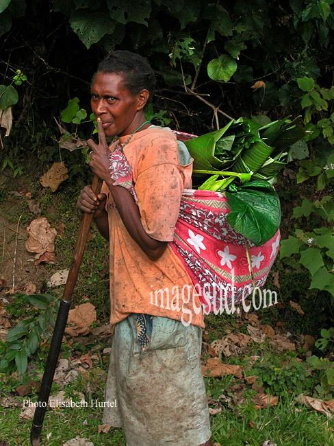Femme des îles du Pacifique sud rentrant de son jardin avec les légumes pour le repas du soir dans son calico sur le dos, Mélanésie