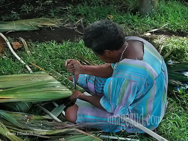 Femme d' Océanie préparant des tuiles végétales pour faire le toit d'une nouvelle maison