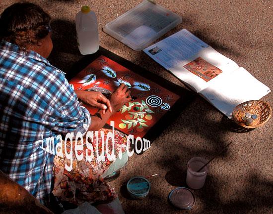 Artiste aborigène d'Australie peignant sur le trottoir d'une grande ville.