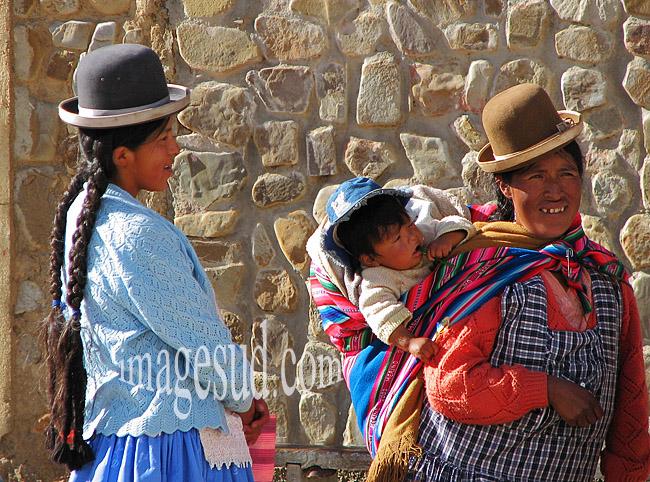 Femme et son enfant sur le dos, accompagnée d'une jeune fille, Bolivie, altiplano des Andes, pays Aymara