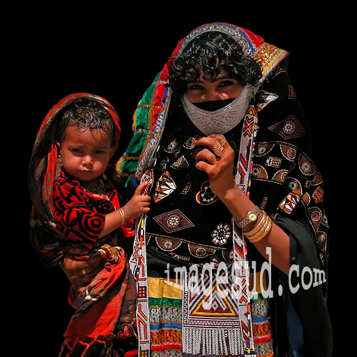 Jeune femme en habit traditionnel portant son enfant, Arabie, tribus nomades