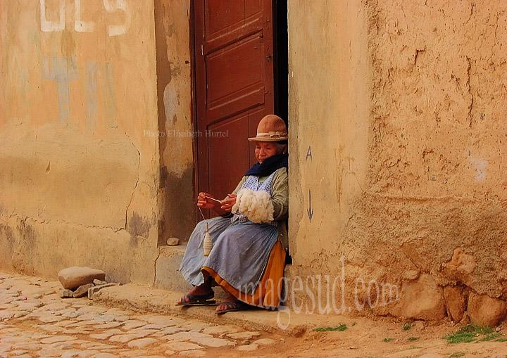 Femme filant la laine sur le pas de sa porte, Bolivie