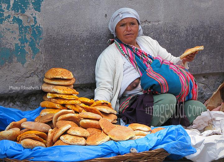 Femme vendant du pain sur le trottoir tout en allaitant son bébé, Bolivie