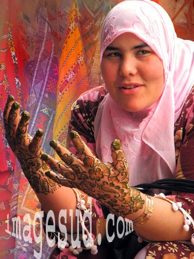 Jeune femme faisant sécher ses mains tatouées au henné, scène de souk, Afrique du Nord