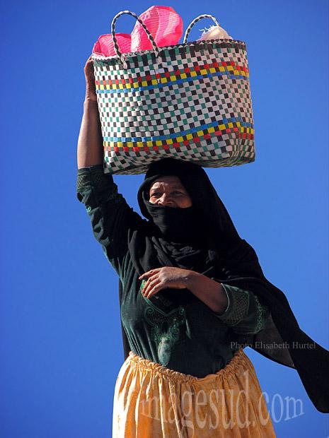 Femme voilée de noir portant un panier sur la tête, Sud Maroc