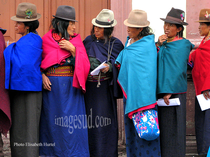 Indiennes des Andes en habits traditionnels faisant la queue devant une administration