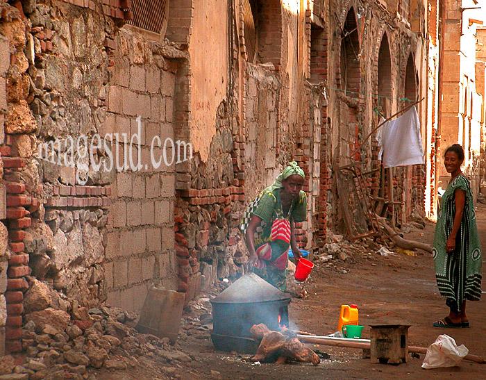 Femme faisant la cuisine dans une rue en ruines, Massawa, Erythrée