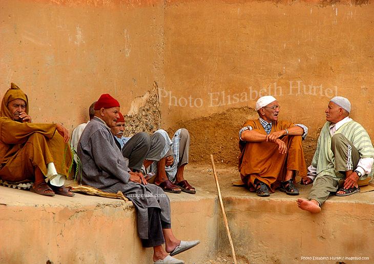 Groupe d'hommes bavardant à l'ombre du rempart, art de la conversation, Taroudant, Maroc