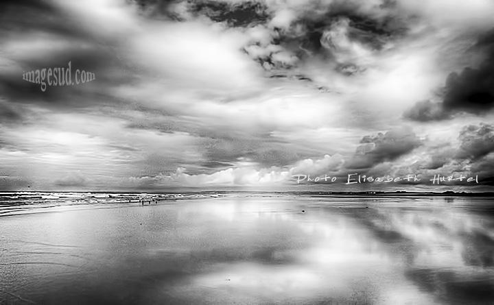 La mer et la plage, sous un ciel nuageux