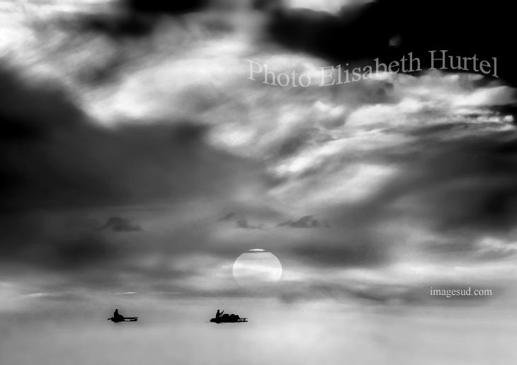 Pirogues à balancier sur un lagon au coucher du soleil, photo noir et blanc