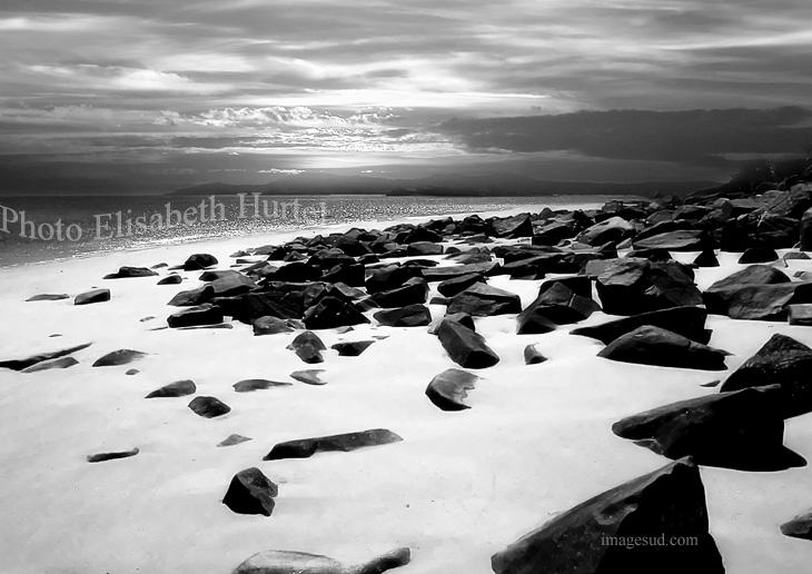 Plage blanche et rochers noirs, photo en noir et blanc