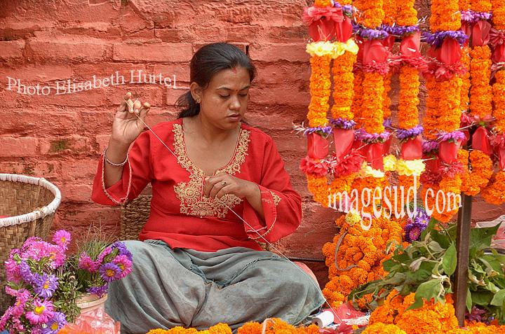 Nepal, Durbar square : confection de guirlandes de fleurs. market scene in katmandu.