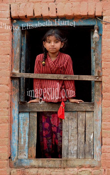 Nepal : fillette à sa fenêtre au village de Panauti, vallée de Katmandou